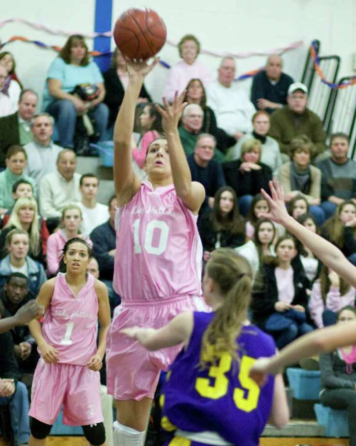 Danbury's Casey Smith pops a jump shot over Westhill's Allison Schechter during the Cancer Awareness game Friday night at Danbury High School. Photo: Barry Horn / The News-Times Freelance
