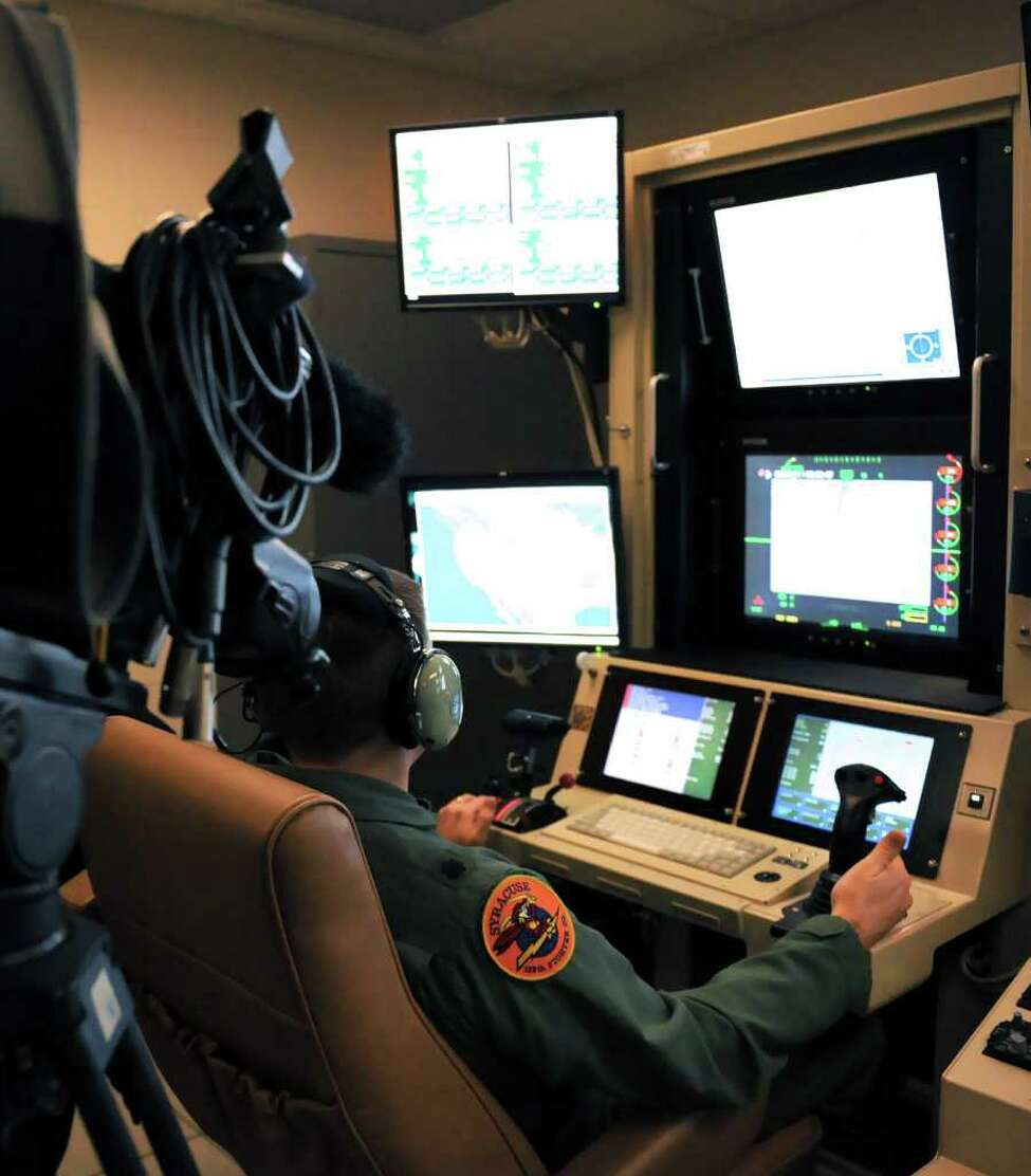 An Air Force lieutenant colonel displays MQ-9 Reaper Remotely Piloted Aircraft control for local media at Hancock Field in Syracuse in 2009. The 174th Fighter Wing plans unmanned flights over the Adirondacks for training purposes. (US Air Force / Tech. Sgt. Jeremy M. Call)