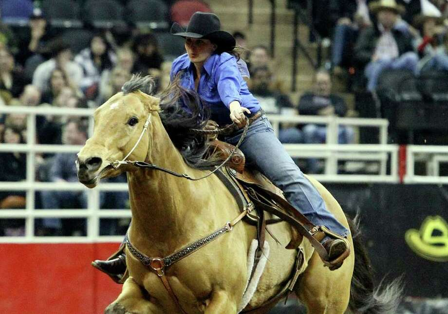 Savanah Reeves of Cross Plains, Texas competes in the barrel racing competition at the 2011 San Antonio Stock Show & Rodeo at the AT&T Center on Friday, Feb. 11, 2011. Reeves' husband, Matt, also participates in rodeos by competing in steer wrestling. Kin Man Hui/kmhui@express-news.net Photo: KIN MAN HUI, SAN ANTONIO EXPRESS-NEWS / kmhui@express-news.net