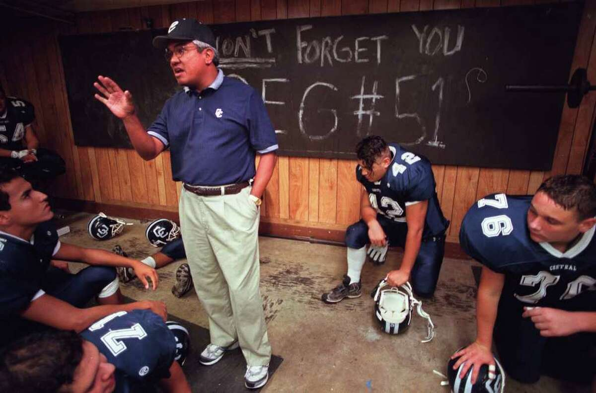 ADVANCE FOR FOOTBALL SECTION-- Central Catholic Football head Coach Carlos Enrico talks to his troops during halftime. On the blackboard behind Enrico the phrase