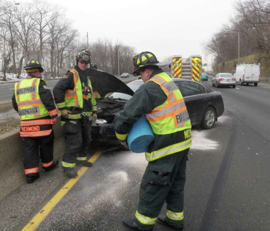 Westport firefighters apply absorbents to the road surface at the site of a single-car crash Saturday on Interstate 95 in Westport. Photo: Contributed Photo/Westport Fire Department;Contributed Photo, Contributed Photo/Westport Fire Department / Westport News contributed