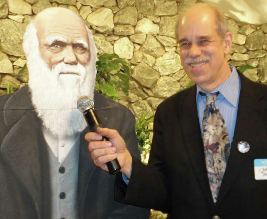 Questioning Darwin -- or at least a cardboard cutout of the legendary naturalist -- is Cary Shaw, the co-chairman of the committee that planned Friday's Darwin Day dinner on the 202nd anniversary of his birth. Photo: Meg Barone / Westport News freelance