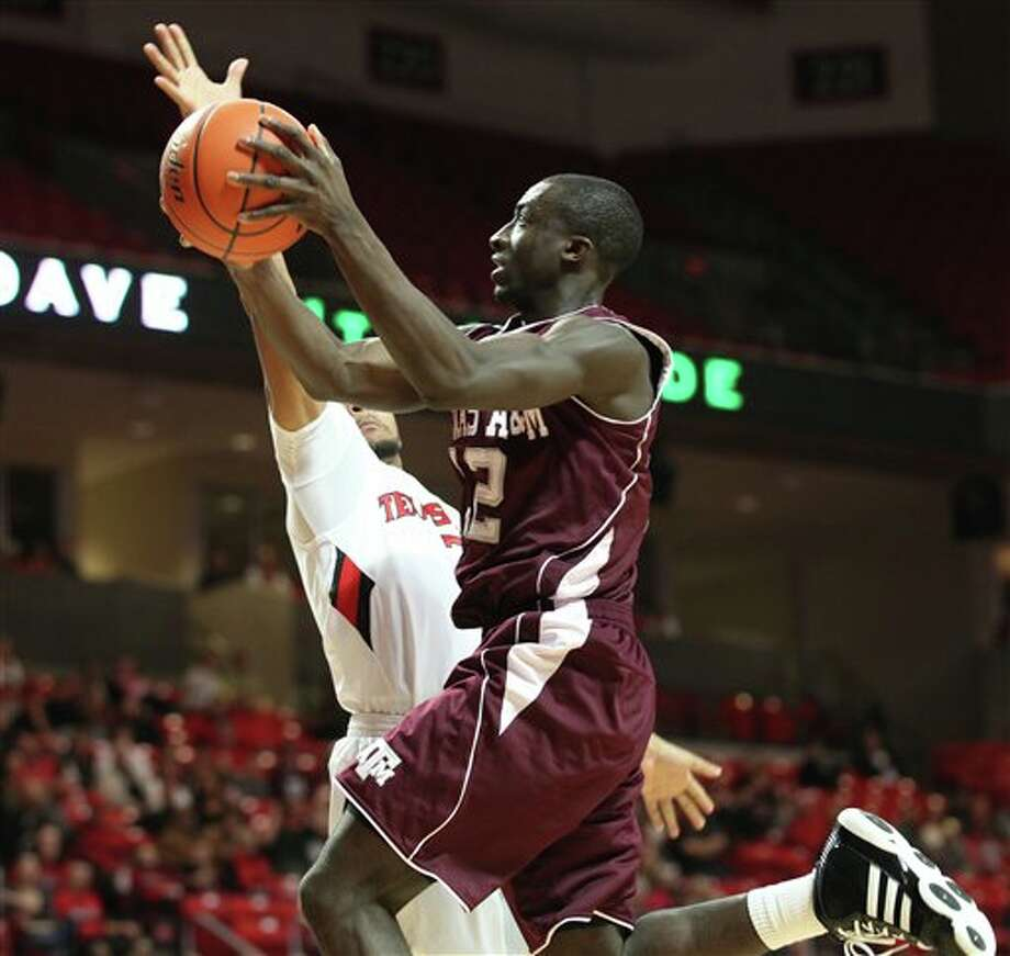 Texas A&M's Andrew Darko drives past Texas Tech's Javarez Willis on Saturday in Lubbock. Photo: Zach Long/Associated Press / AP