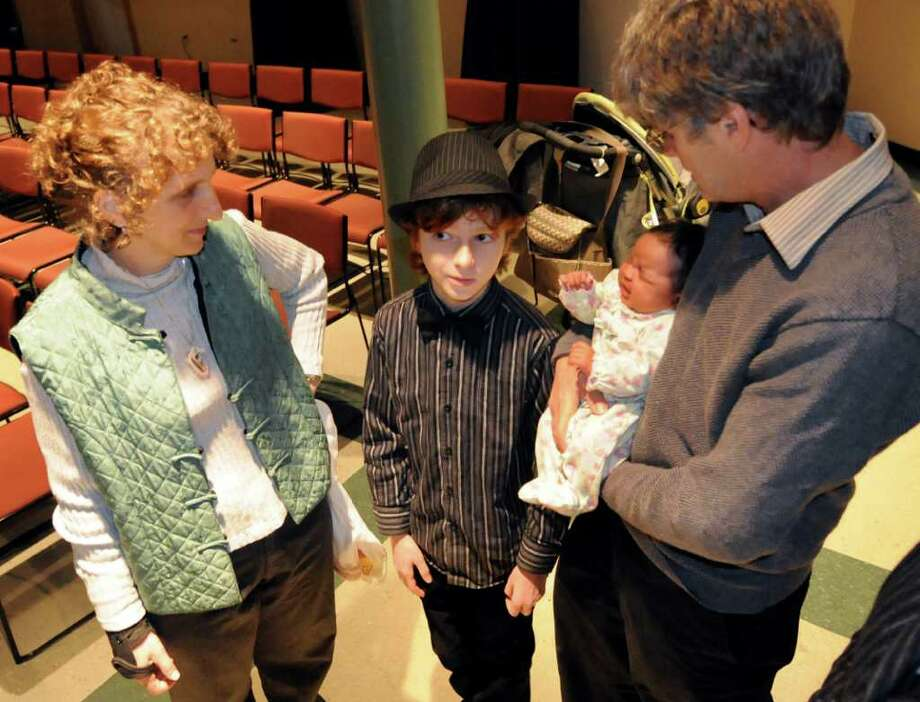 Julian Foy, 11, of Troy, center, talks about his musical interests with his mother, Deyva Arthur, left, father, Wayne Foy, and 1-month-old sister, Serena, during the second annual Tchaikovsky Piano Competition on Saturday in Albany. (Cindy Schultz / Times Union Photo: Cindy Schultz