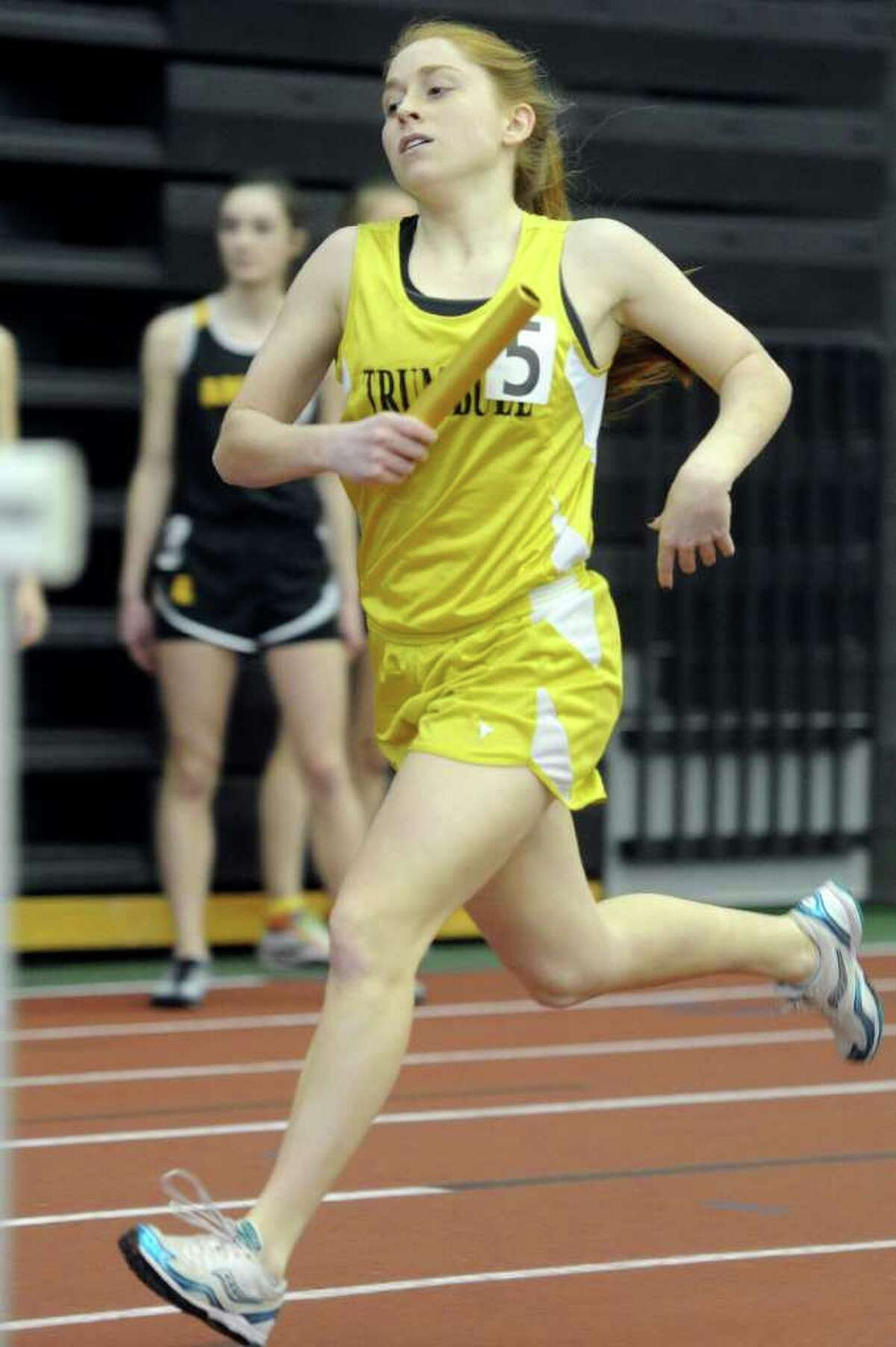Trumbull's Emily Riehl runs in the 4x800 relay during Saturday's Class LL track championship meet at the New Haven Athletic Center on February 12, 2011.