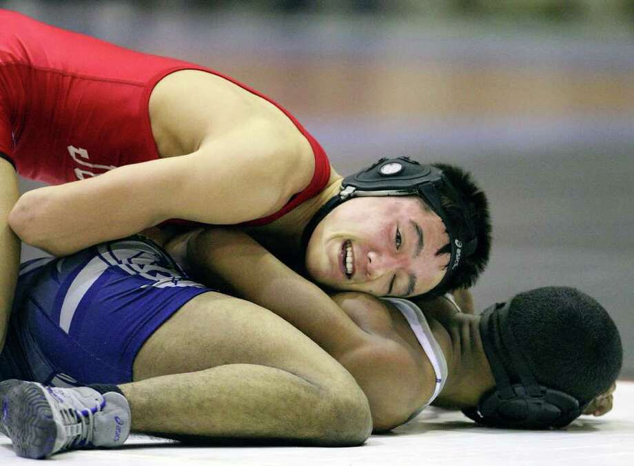 FOR SPORTS - Judson's Aaron Walker (top) controls Bryan's Victor Thomas in the 140 weight class Saturday Feb. 12, 2011 during the Region IV wrestling tournament held at Littleton Gymnasium.  Walker won the match and placed first. Thomas placed second. (PHOTO BY EDWARD A. ORNELAS/eaornelas@express-news.net) Photo: EDWARD A. ORNELAS, SAN ANTONIO EXPRESS-NEWS / eaornelas@express-news.net