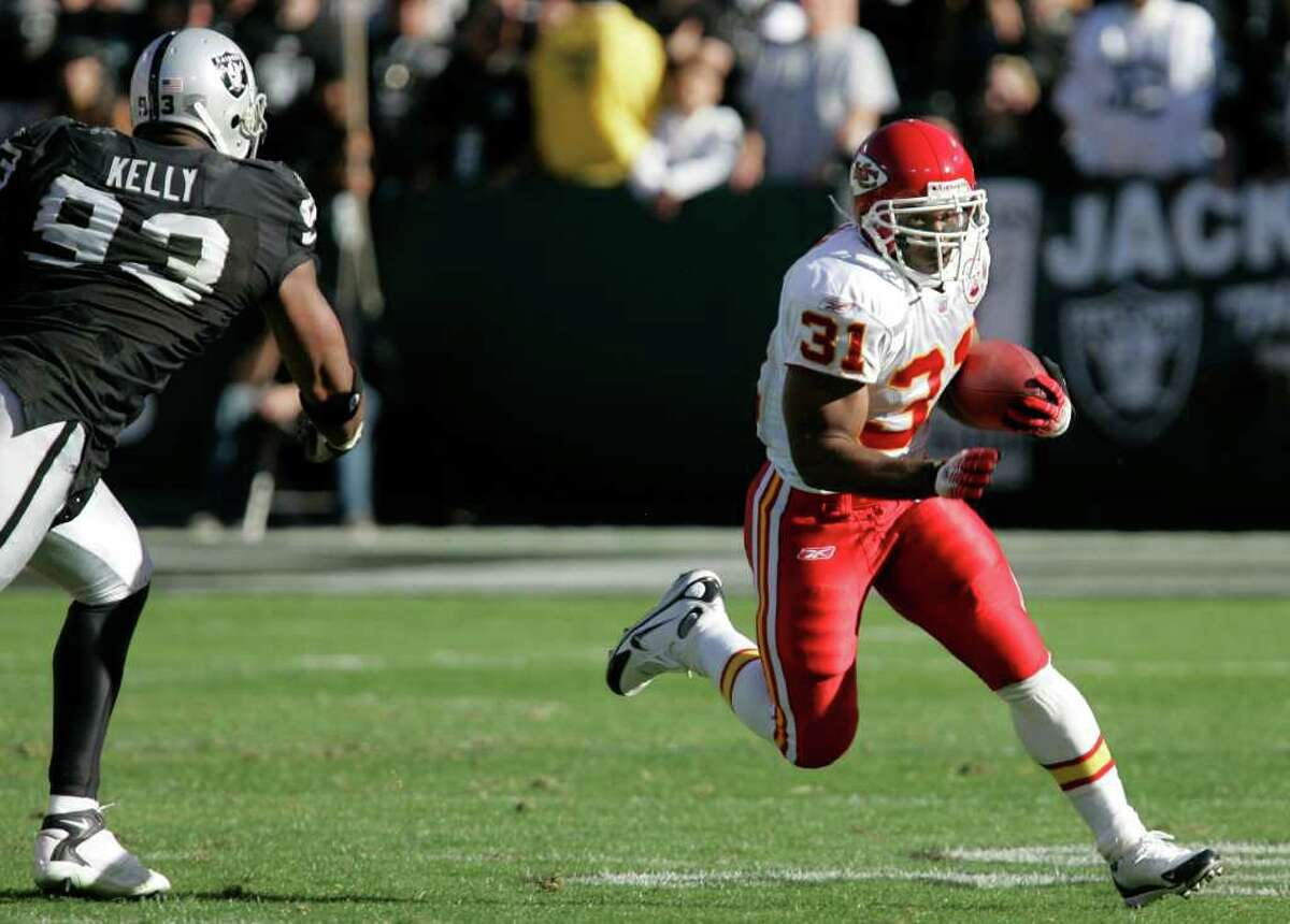 Kansas City Chiefs running back Priest Holmes (31) runs in front of Oakland Raiders defensive end Tommy Kelly (93) in the fourth quarter of their NFL football game in Oakland, Calif., Sunday, Oct. 21, 2007. The Chiefs defeated the Raiders, 12-10.