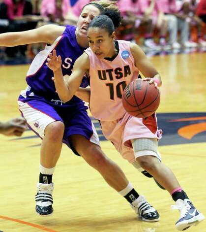 SPORTS   Roadrunner guard Amber Gregg drives around Cheyenne Berry as the UTSA women play Stephen F. Austin at the UTSA Convocation Center on February 12, 2011. Tom Reel/Staff Photo: TOM REEL, SAN ANTONIO EXPRESS-NEWS / © 2011 San Antonio Express-News