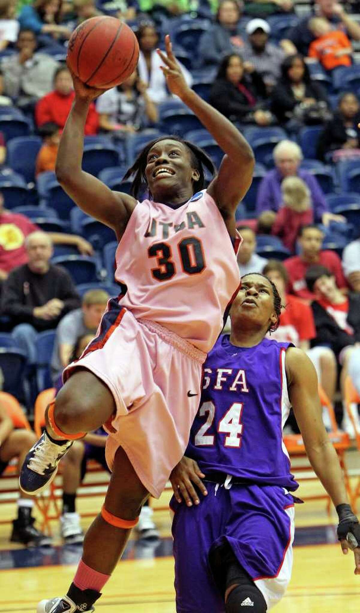SPORTS Roadrunner forward Ijeoma Waturuocha gets free to the hoop against Decreasha Goodner as the UTSA women play Stephen F. Austin at the UTSA Convocation Center on February 12, 2011. Tom Reel/Staff