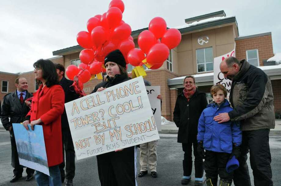 Bethlehem Middle School student Jeremy Luzinski, center, holds a sign Sunday to protest the planned construction of a cell phone tower a few hundred feet from the Eagle Elementary School, which is behind him, in Bethlehem. ( Philip Kamrass / Times Union ) Photo: PHILIP KAMRASS