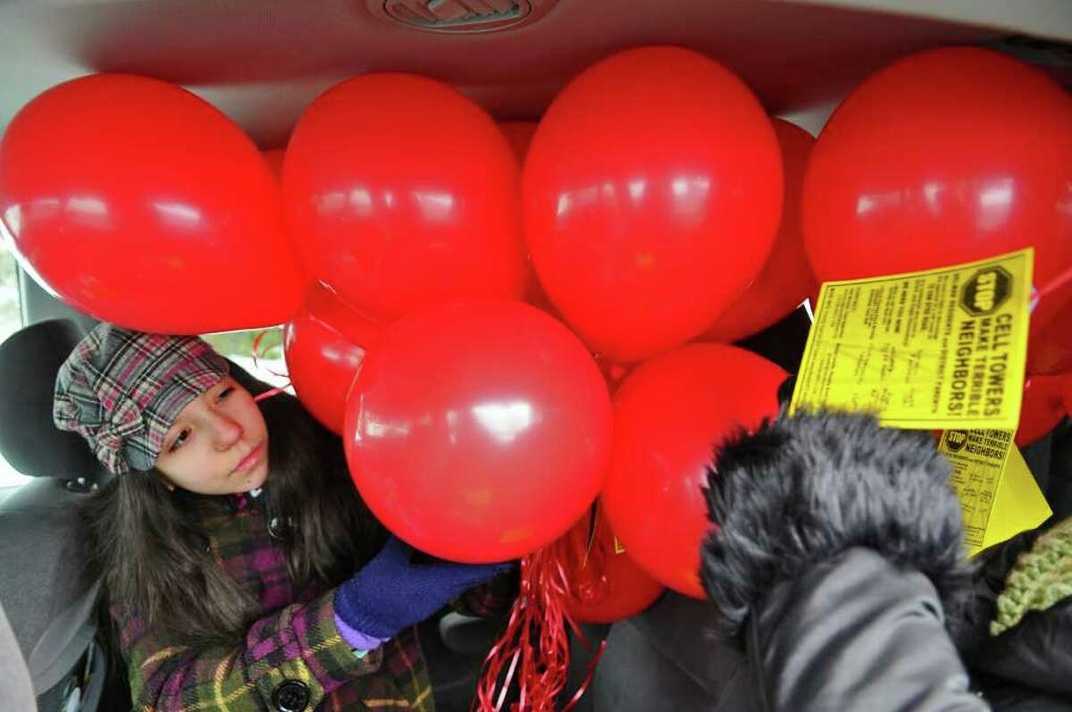 Bethlehem Middle School student Maya Martinez helps to deliver protest balloons Sunday against the planned construction of a cell phone tower a few hundred feet from the Eagle Elementary School and the high school across the street. ( Philip Kamrass / Times Union )