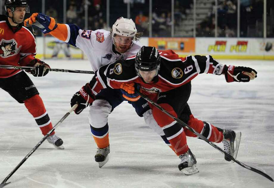 Sound Tiger Robin Figren, left, chases the puck into the corner with Portland's Brian O'Hanley in the second period of their game at the Webster Bank Arena in Bridgeport on Sunday, February 13, 2011. Photo: Brian A. Pounds / Connecticut Post