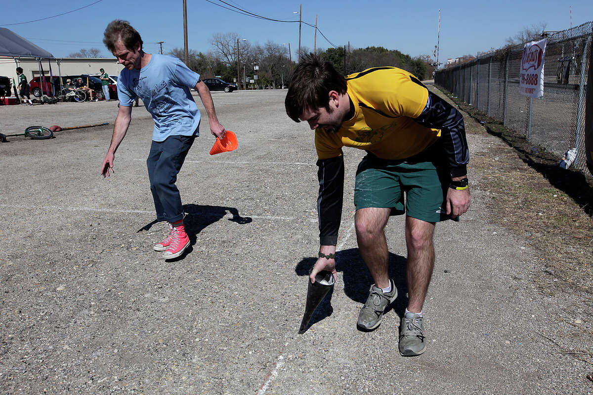 Unicycle Football League founder Marcus Garland, left, and The Ill-Eagles team member Daniel McCarthey prepare the field as before a game against the Gnarwhals at the Farmer's Market parking lot in San Marcos, Texas, Sunday, Feb. 13, 2011.