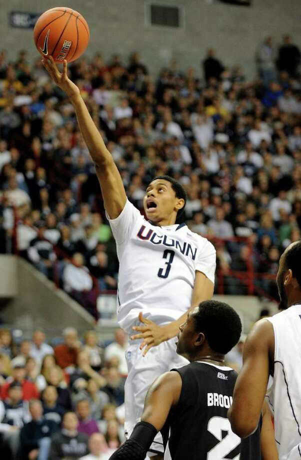 Connecticut's Jeremy Lamb, center, drives past Providence's Marshon Brooks during the second half of Connecticut's 75-57 victory in their NCAA college basketball game in Storrs, Conn., on Sunday, Feb. 13, 2011. Brooks scored a game-high 25 points in his team's loss.  (AP Photo/Fred Beckham) Photo: AP