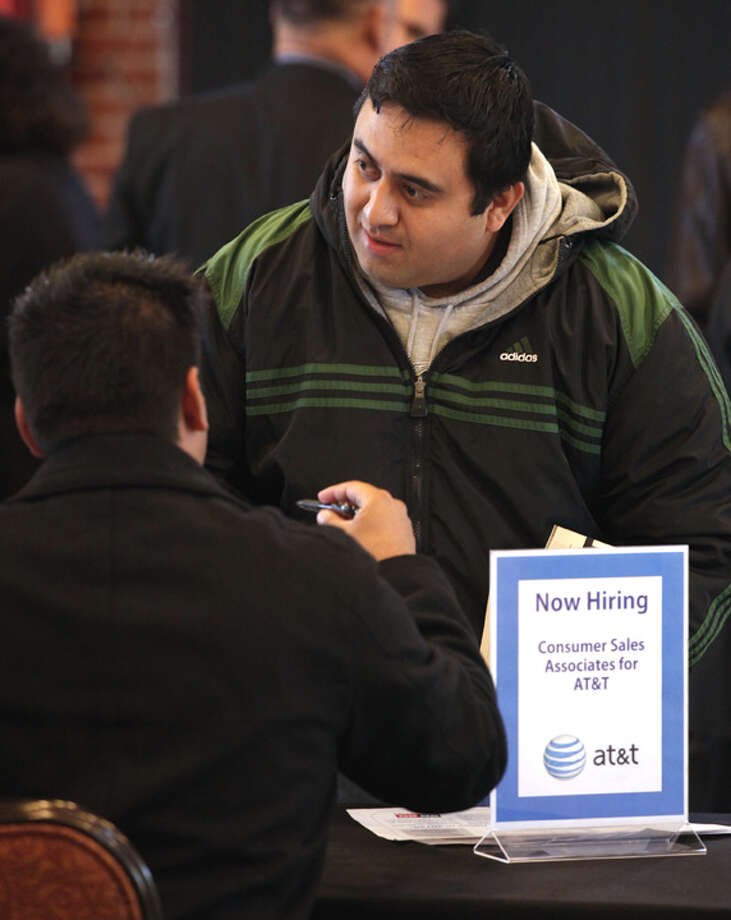 Ex-Marine Enrique Alcantara (right) talks to Nesto Cruz of 20/20 Companies at a job fair at Sunset Station. The jobless rate for vets who served after September 2001 was 15.2 percent last month, the highest level the government has tracked. Photo: Bob Owen/rowen@express-news.net
