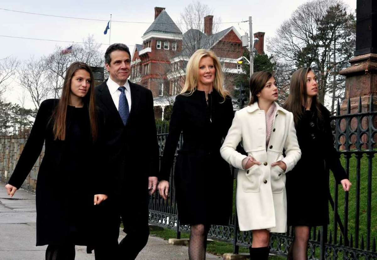 New York's new Governor Andrew Cuomo walks from the Governor's Mansion, pictured in the background, to the Cathedral of the Immaculate Conception, in Albany, New York, to attend services with his girlfriend, Sandra Lee, center, and his daughters, from left, Cara, Michaela, and Mariah, Sunday, Jan. 2, 2011. (AP Photo/Stewart Cairns)