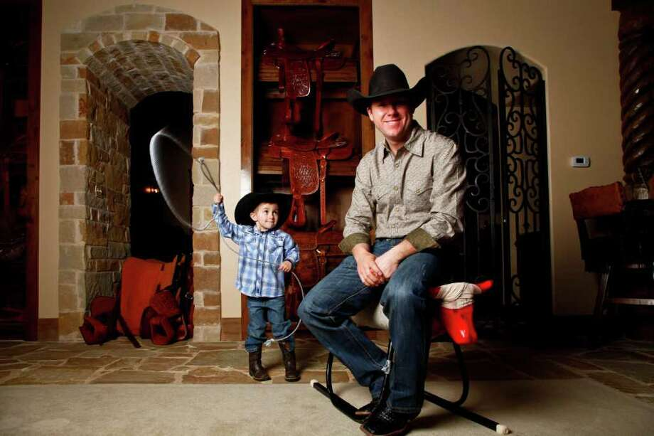 Trevor Brazile poses for a portrait next to a handful of his 8 PRCA All-Around World Title saddles, as his son, Treston, 3, ropes him while at the family home, Sunday, Feb. 6, 2011, in Decatur.   Trevor Brazile is a tie-down and team roper and won 14 world champion titles bestowed by the Professional Rodeo Cowboy Association. He is an eight-time winner of the all-around gold buckle, giving him an edge over fellow Texas Ty Murray. He is on his way to his 15th title and is making his way through this season's Texas rodeos in pursuit of that goal. He has appearances in Fort Worth in January, San Antonio in February and Houston in March.   ( Michael Paulsen / Houston Chronicle ) Photo: Michael Paulsen, Staff / Houston Chronicle