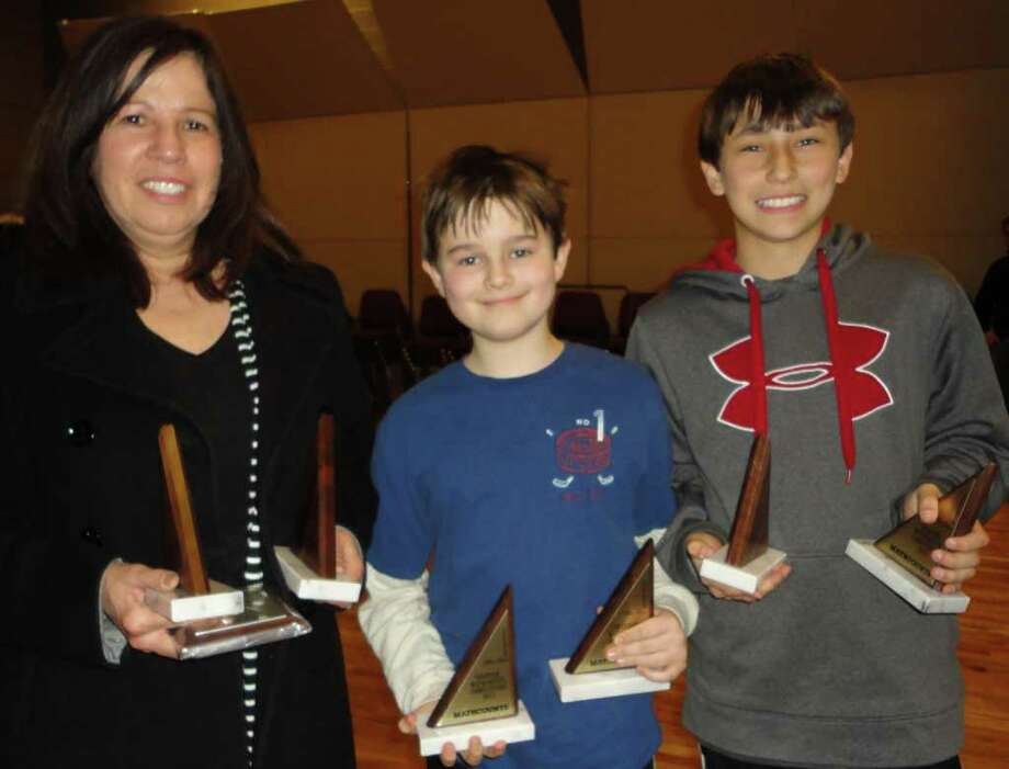 Coleytown Middle School math teacher Connie Jones and students Zachary Kornbluth, a sixth-grader, and Matt Kaye, a seventh-grader, collect their overall fourth-place trophies in the MathCOUNTS competition Saturday at Fairfield University. Photo: Meg Barone / Westport News freelance