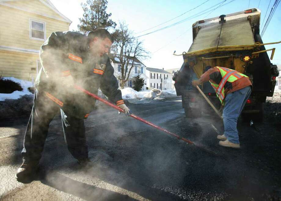Public works employees Nick Alamo, left, and Shuiwa Turner patch potholes on Beechmont Avenue in Bridgeport on Thursday, February 10, 2011. Photo: Brian A. Pounds / Connecticut Post
