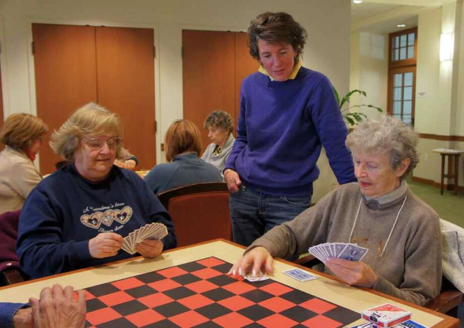 Sue Pfister, director of the Westport Center for Senior Activities, looks on as Carol Malone, left, and Woody Lysobey, right, play a game of pinochle at the center on Friday, Feb. 11, 2011. Photo: Paul Schott / Westport News