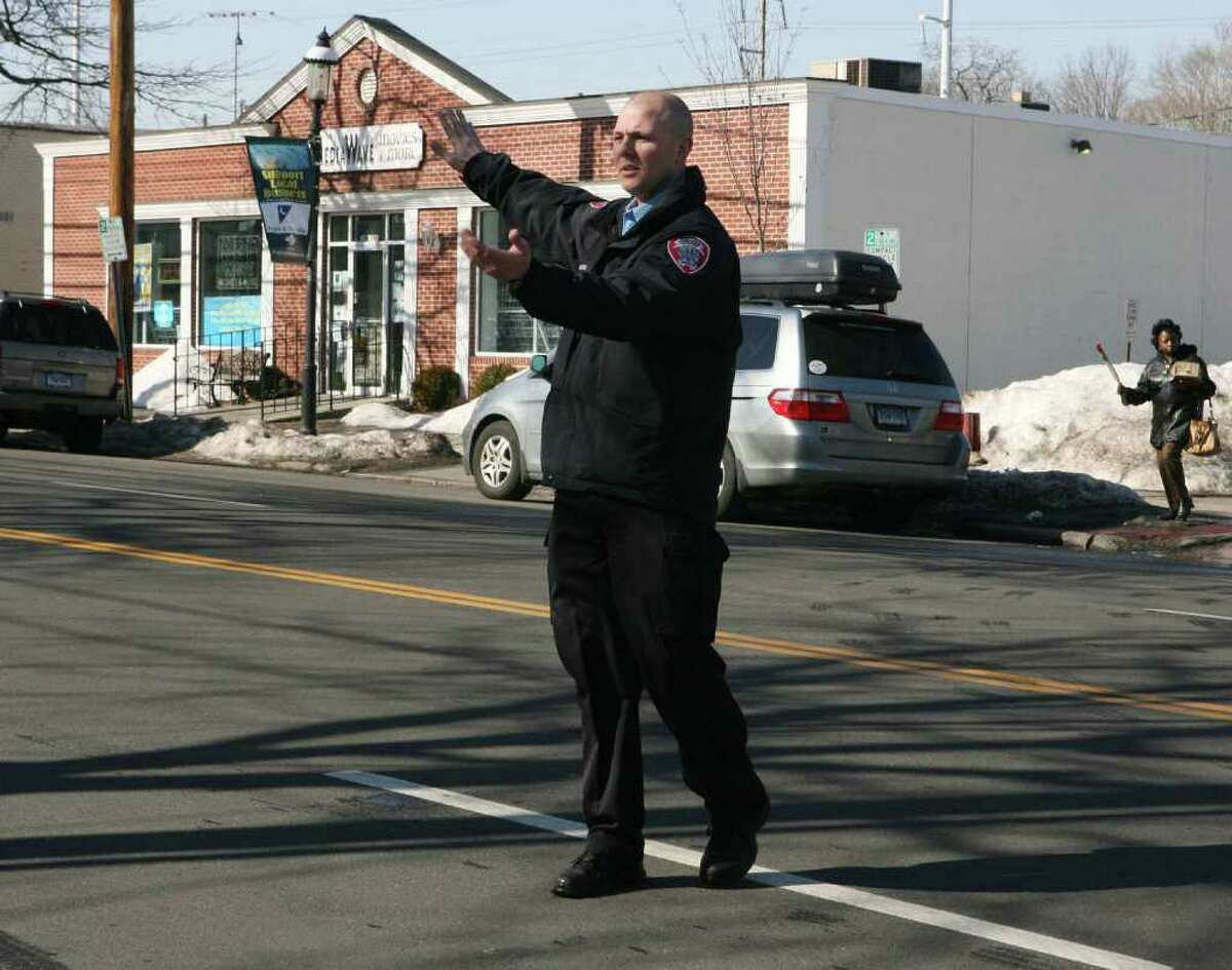 Fairfield Police department Special Agent Sean Grabowski directs a car out of a difficult parking lot onto the Post Road in downtown Fairfield on Monday, Feb. 14, 2011. Grabowski walks the downtown area assisting people, checking parking, and making sure that businesses are secured in the evening.