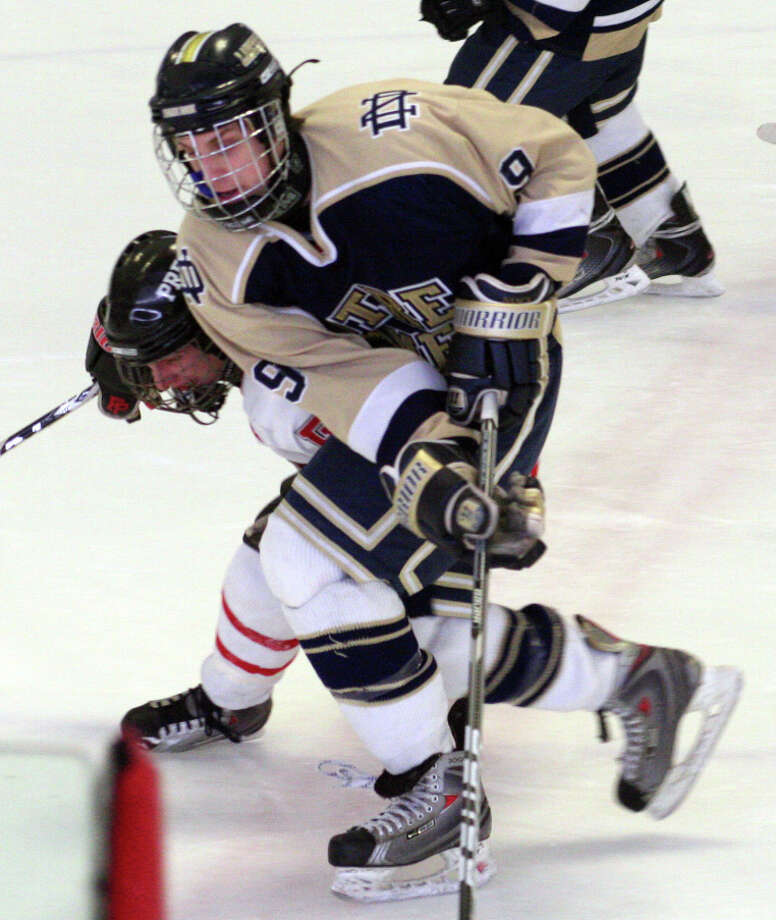 Notre Dame-Fairfield's Brian Sanca is ridden toward the boards by Prep's Sean Henry during the Jesuits' 2-0 win over the Lancers on Saturday at Wonderland of Ice. Photo: Tim Parry / Fairfield Citizen freelance