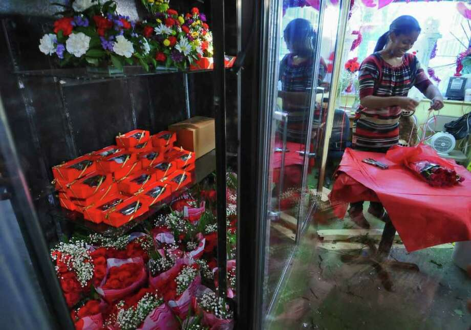 Shanelle Carter, co-owner of Taysha Florist, wraps roses for a customer in her family's shop in Albany, NY on Sunday February 13, 2011, in preparation for Valentine's Day on Monday. ( Philip Kamrass / Times Union ) Photo: PHILIP KAMRASS