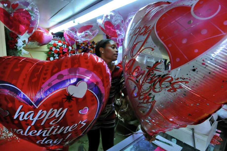 Shanelle Carter, co-owner of Taysha Florist, prepares mylar balloons for  a customer in her family's shop in Albany on Sunday, Feb. 13, 2011.  Photo: PHILIP KAMRASS