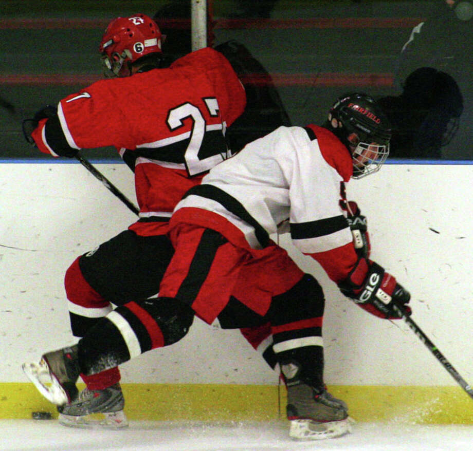 Fairfield's Chris Stern and Greenwich's Craig Mackin battle for the puck in the Cardinals' 2-0 win over the Mustangs on Saturday night at Wonderland of Ice. Photo: Tim Parry / Fairfield Citizen freelance