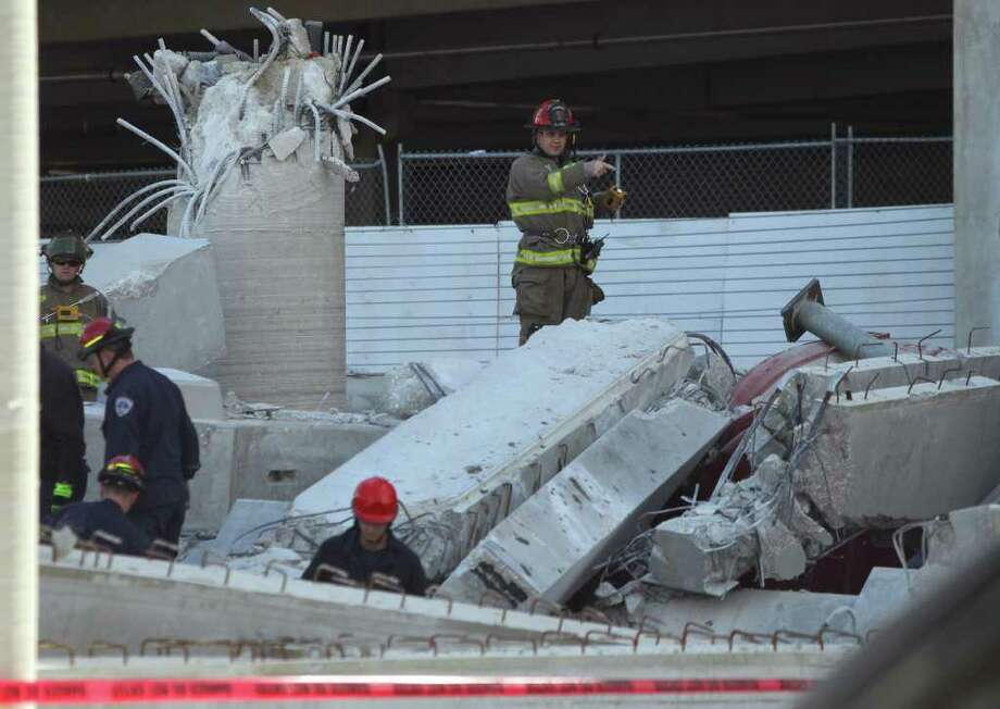San Antonio firefighters inspect the rubble of a parking garage that collapsed Monday February 14, 2011 at the corner of Medical and Wurzbach. Two workers were injured. Photo: JOHN DAVENPORT, SAN ANTONIO EXPRESS-NEWS / jdavenport@express-news.net