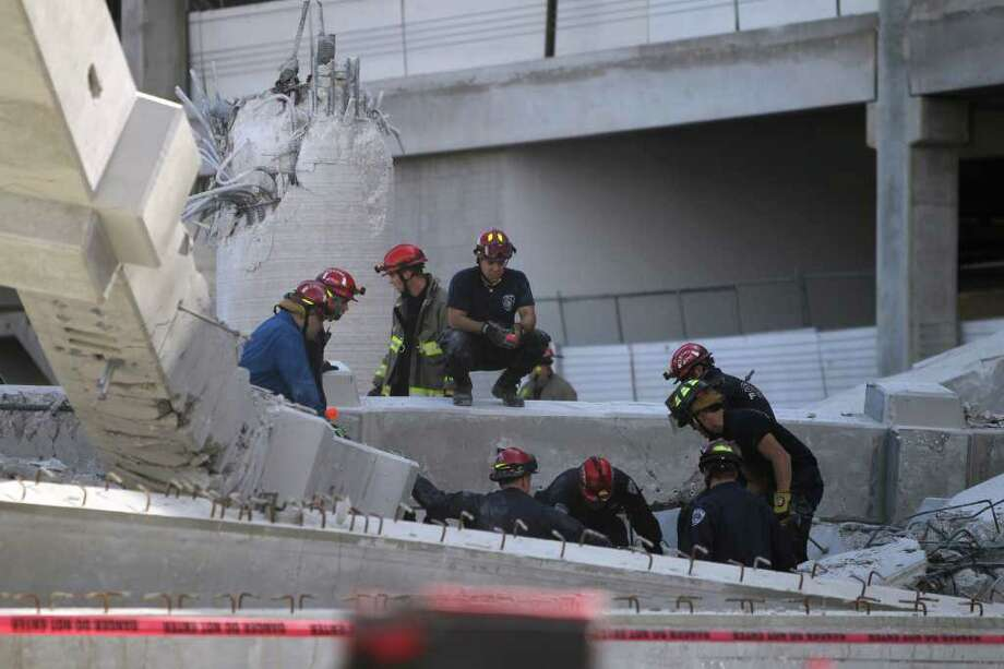 Firefighters look in the rubble of the parking garage that collapsed Monday February 14, 2011. Two workers were injured in the accident. Photo: JOHN DAVENPORT, SAN ANTONIO EXPRESS-NEWS / jdavenport@express-news.net