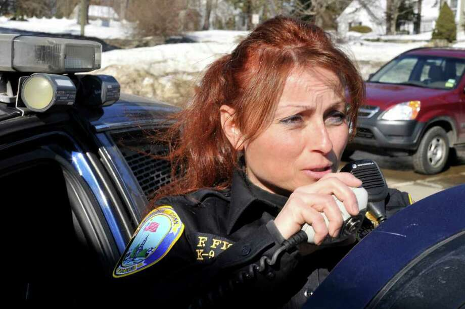 Newtown Police Officer Felicia Figol talks with the dispacher on her patrol car radio Monday, Feb. 14, 2011. Photo: Michael Duffy / The News-Times