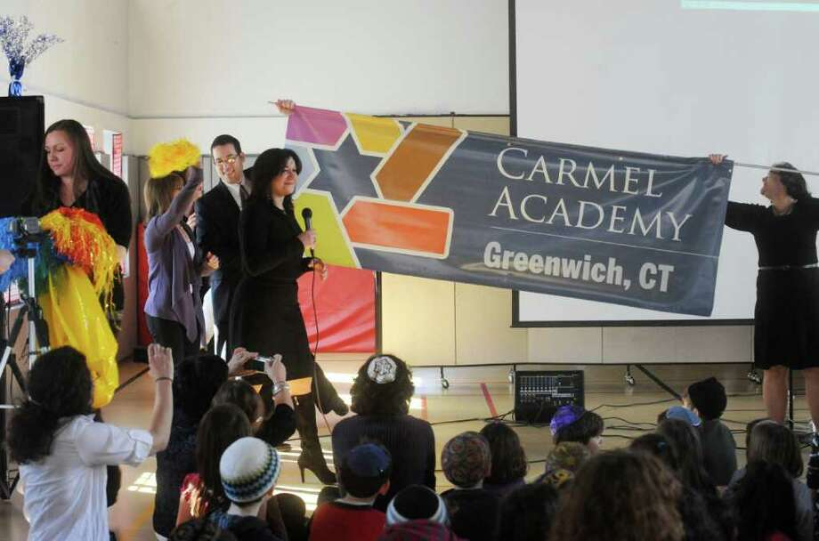 Seth Young, director of development, left, and Head of School Nora Anderson, with a banner of the Westchester Fairfield Hebrew Academy's new name, Carmel Academy, on Monday, Feb. 14, 2011.  Erica Sokoloff, director of Jewish life, holds the banner at right. Photo: Helen Neafsey / Greenwich Time