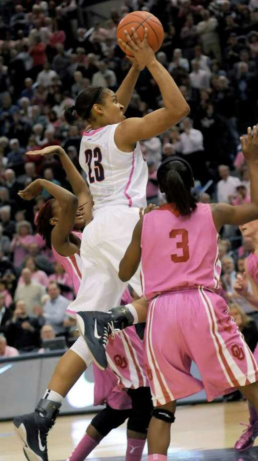 Connecticut's Maya Moore (23) shoots as Oklahoma's Aaryn Ellenberg (3) watches during the first half of an NCAA college basketball game in Hartford, Conn., Monday, Feb. 14, 2011. (AP Photo/Bob Child) Photo: AP