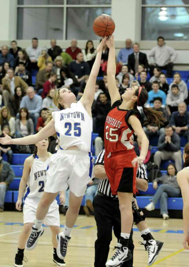 Newtown's Lauren Baranowski, left, and Pomperaug's Sara Pettinelli reach for the tip off at Monday nights game at Newtown High School. Feb. 14, 2011 Photo: Lisa Weir / The News-Times Freelance