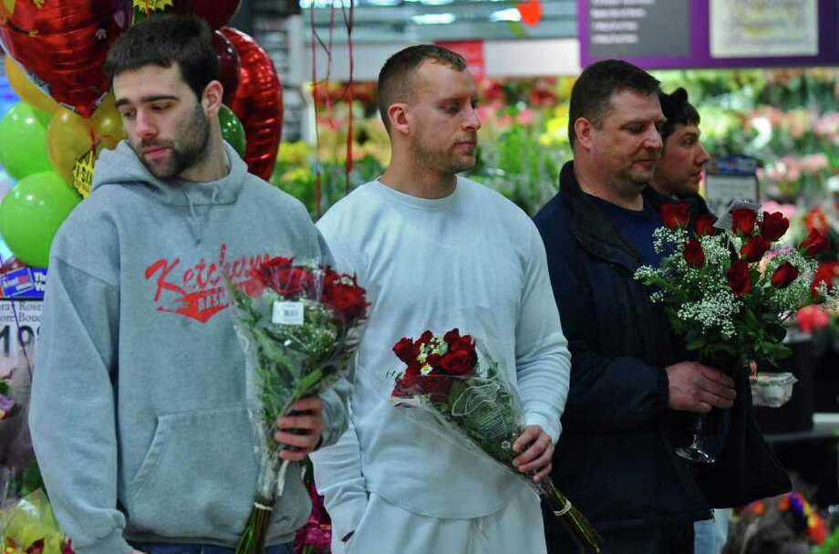 From left, Dave Smith of Albany, John Bonkoski of Cohoes and Ray Beaudoin of Stillwater wait to buy Valentine's Day flowers for their girlfriends at the floral department at the Price Chopper in Latham, NY on Monday February 14, 2011.  ( Philip Kamrass / Times Union ) Photo: PHILIP KAMRASS