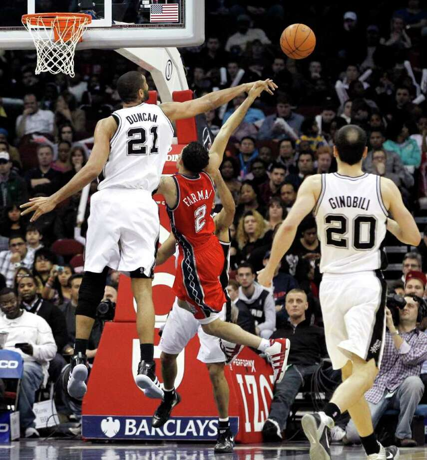 San Antonio Spurs center Tim Duncan (21) deflects a shot by New Jersey Nets guard Jordan Farmar (2) as Spurs' Manu Ginobili (20) looks on during the third quarter of an NBA basketball game, Monday, Feb. 14, 2011, in Newark, N.J. Duncan scored all his 15 points in the first half as the Spurs won 102-85. Photo: AP