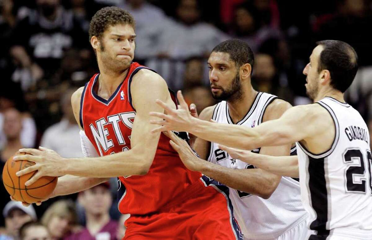 New Jersey Nets' Brook Lopez, left, is doubled teamed by San Antonio Spurs' Tim Duncan, center, Manu Ginobili, of Argentina, during the third quarter of an NBA basketball game, Monday, Feb. 14, 2011, in Newark, N.J. , The Spurs won 102-85. Lopez scored 11 points and had 10 rebounds.