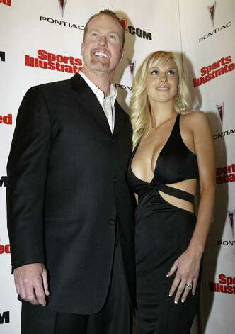 Former baseball star Mark McGwire, left, poses for photographers with his wife Stephanie, during a press conference to promote the new Sports Illustrated Swimsuit Issue in New York Tuesday, Feb. 15, 2005. The couple is featured in the issue. Photo: GREGORY BULL, AP / AP