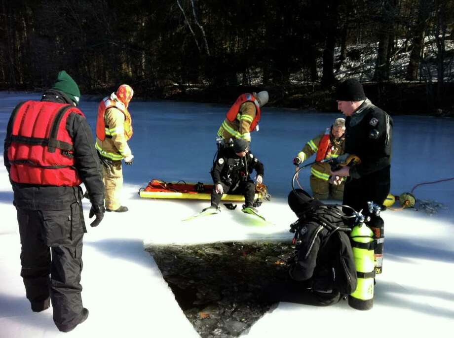 Stamford Fire & Rescue dive team members practice ice rescue skills at the North Stamford Reservoir on Tuesday. Photo: John Nickerson, Contributed Photo / Stamford Advocate