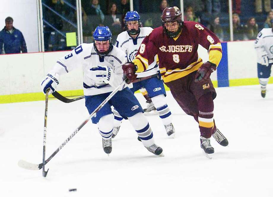 Darien's William Kerr and St. Joseph's John Ferguson battle for control of the puck in boys hockey in Darien, Conn. on Tuesday February 15, 2011. Photo: Kathleen O'Rourke / Stamford Advocate