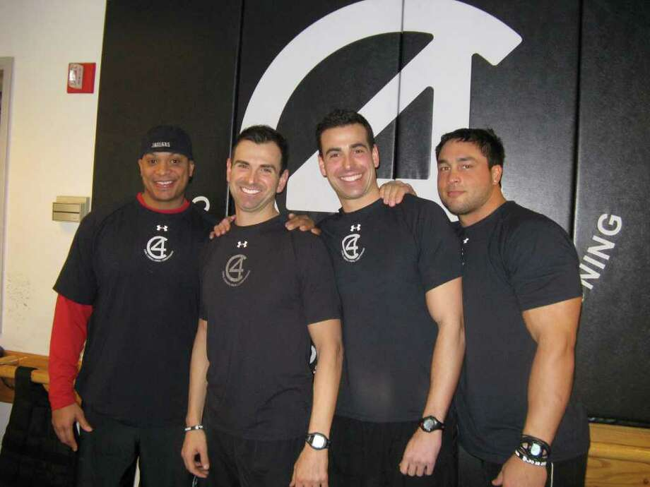 C4 trainers, from left, are former NFL player Vince Workman, world-ranked Ironman and C4 co-owner Craig Vitale, collegiate football player and C4 co-owner Todd Vitale and Arena Football player Karl Pfistner. Brothers Craig and Todd both played football for Greenwich High School. Photo: Contributed Photo / Greenwich Citizen