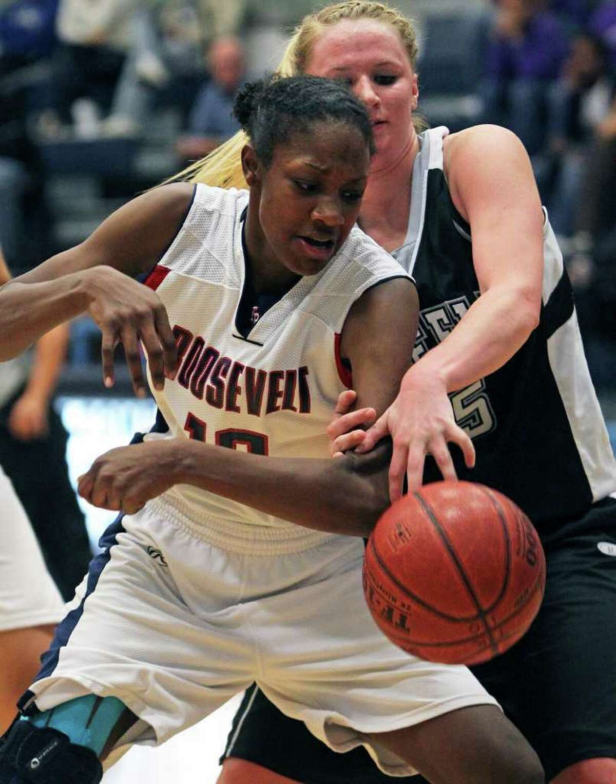 SPORTS Roosevelt's Niaga Mitchell-Cole is fouled in the lane by Rebekah Rightnour as the Steele girls play Roosevelt in 5A high school basketball playoff action at South San gym on February 15, 2011. Tom Reel/Staff