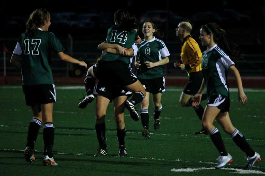 sports - Reagan teammates Caitlin Owen (#14) and Ashley Crabbe (9) embrace, center, as they celebrate their win over MacArthur with their teammates Julia Rice, from left, Kristen Arteaga and Christine Carrera at Comalander Stadium in San Antonio on Tuesday, Feb. 15, 2011. LISA KRANTZ/lkrantz@express-news.net Photo: Lisa Krantz, SAN ANTONIO EXPRESS-NEWS / lkrantz@express-news.net