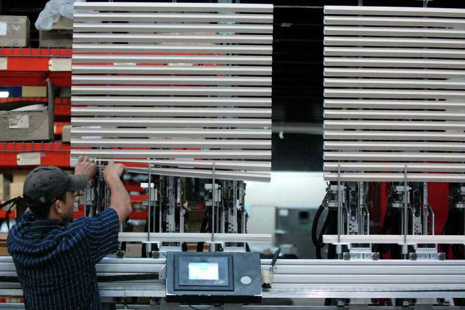 One of Comfortex's newest employees works a the robotic crimping machines in the production of window blinds at their plant in Watervliet Tuesday 9/14/2010. ( Michael P. Farrell / Times Union ) Photo: Michael P. Farrell / 00010264A
