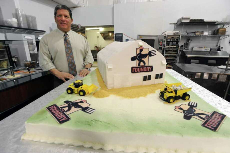 Angelo Mazzone stands next to a huge cake inside The Foundry at Globalfoundries in Malta, NY on February 15, 2011.  Angelo Mazzone Catering is celebrating the one-year anniversary of The Foundry, the on-site dining dome at GlobalFoundries. It feeds 1,000 meals a day. (Lori Van Buren / Times Union) Photo: Lori Van Buren