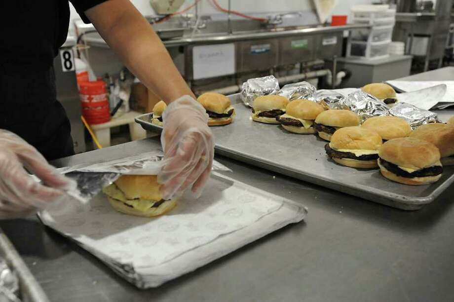 Workers wrap hamburgers inside The Foundry, at Globalfoundries in Malta, NY, before lunch time on February 15, 2011.  Angelo Mazzone Catering is celebrating the one-year anniversary of The Foundry, the on-site dining dome at GlobalFoundries. It feeds 1,000 meals a day. (Lori Van Buren / Times Union) Photo: Lori Van Buren