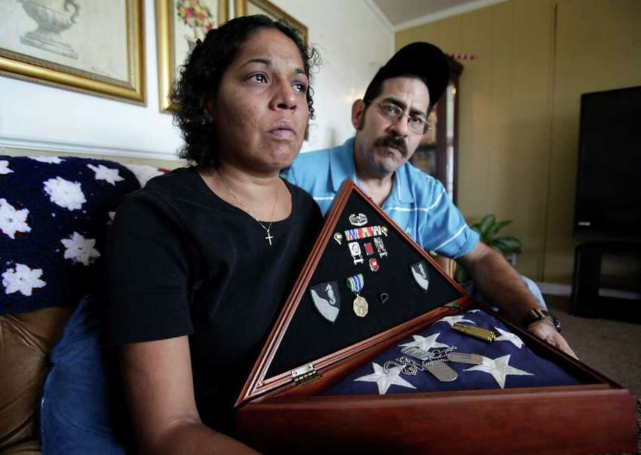 "Amelia Aguilar's eyes fill with tears as she sits with her husband Armando Aguilar in their Blessing home, holding items from the military service of their son, Armando ""Mondo"" Aguilar Jr. His death in 2010 was ruled a suicide. Photo: BOB OWEN / SAN ANTONIO EXPRESS-NEWS"