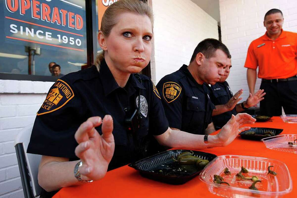 METRO - San Antonio Police Officer Melisse Turner maintains her composure as time runs out as she and fellow officers, David Bierman, center, and Mark Bishop compete against members of the San Antonio Fire Department in the second annual Jalapeno Eating Contest sponsored by Whataburger, Tuesday, Feb. 15, 2011. SAFD took the honors by eating 23 peppers while the police department came in at 19 peppers. Each of the contestants was given 10 peppers to eat in sixty seconds. First place won $750 while second place was $250 with the prize money going to the 100 Club of San Antonio. The non-profit helps support families of firefighters and peace officers who die in the line of duty. JERRY LARA/glara@express-news.net