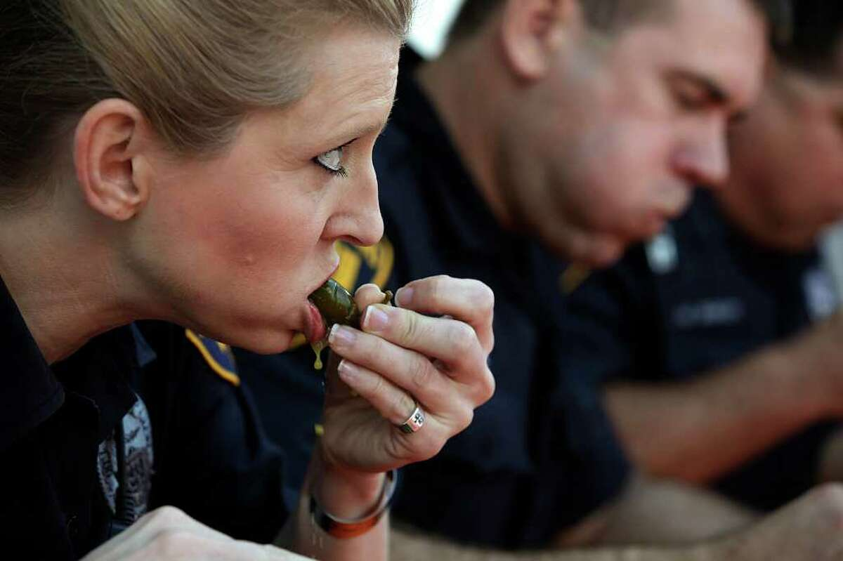 METRO - San Antonio Police Officer Melisse Turner works on a pepper as she and fellow officers, David Bierman, center, and Mark Bishop compete against members of the San Antonio Fire Department in the second annual Jalapeno Eating Contest sponsored by Whataburger, Tuesday, Feb. 15, 2011. SAFD took the honors by eating 23 peppers while the police department came in at 19 peppers. First place won $750 while second place was $250 with the prize money going to the 100 Club of San Antonio. The non-profit helps support families of firefighters and peace officers who die in the line of duty. JERRY LARA/glara@express-news.net